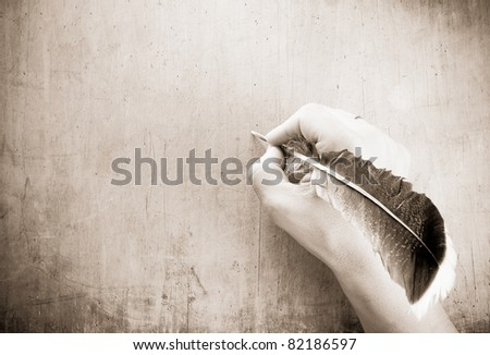 writing hand and pen feather on wood background - stock photo