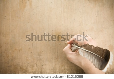 writing hand with pen feather at old wood background texture - stock photo
