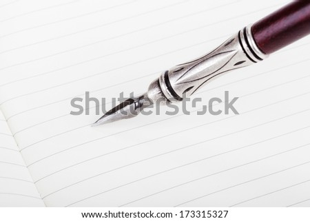 Writing in a text book with luxury retro ink pen - stock photo