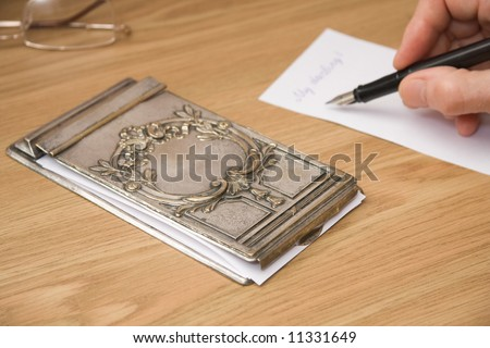 writing note near vintage silver notebook cover with patina for paper storing - stock photo