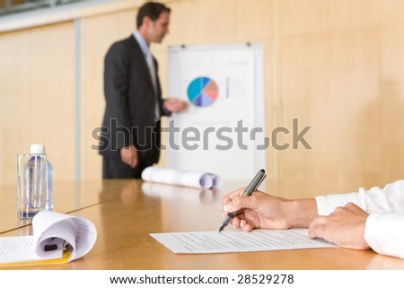 writing notes at a boardroom meeting - stock photo