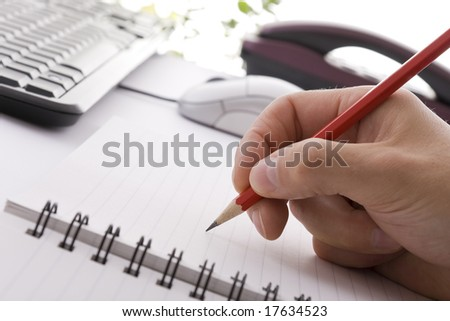 Writing on a notepad with a pencil - stock photo