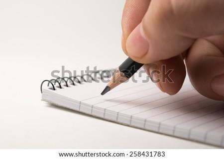 Writing on notepad. close up, isolated on white background - stock photo