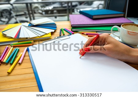 Writing with color pencil on the white sheet with paper samples and colorful books on the background on the wooden table - stock photo