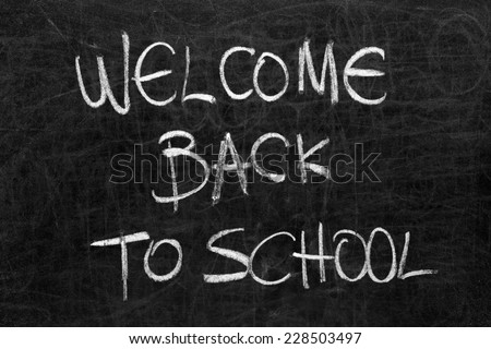 Written welcome back to school on the blackboard with white chalk - stock photo