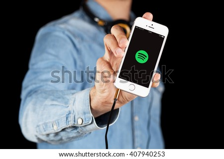 WROCLAW, POLAND - APRIL 12, 2016: Apple iPhone SE smartphone with music streaming app Spotify on screen - stock photo