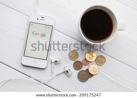 WROCLAW, POLAND - JULY 31, 2014: Photo of iPhone 4 smartphone device with a Google search app running - stock photo