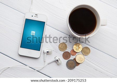 WROCLAW, POLAND - JULY 31, 2014: Photo of iPhone 4 smartphone device with Linkedin app running - a social network for professionals - stock photo