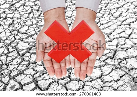 wrong icon in hand on soil crack .clipping path.Earth day concept - stock photo