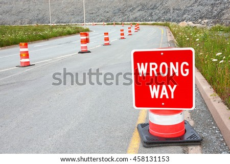 Wrong way traffic sign and safety cones. - stock photo