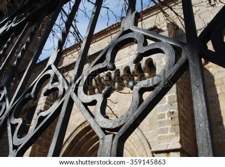 Wrought black iron fence with ironwork - stock photo