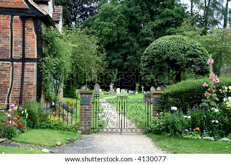 Wrought Iron Entrance Gate to an English Village Churchyard with flowers and Timber Framed Cottage - stock photo