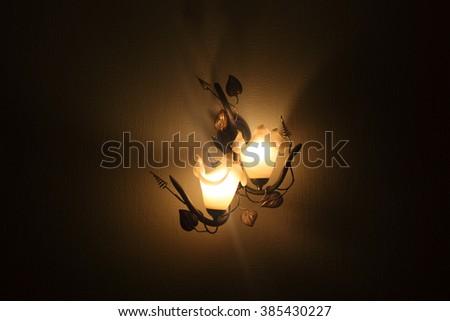 wrought-iron lamp shines at night - stock photo