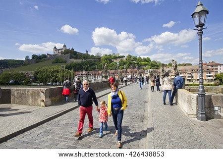 Wurzburg, Germany - May 4, 2014: Couple with their grandchild and other people cross the old Main Bridge below Marienburg Castle in Wurzburg, Germany on May 4, 2014 - stock photo