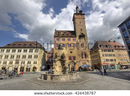 Wurzburg, Germany - May 4, 2014: People walk on the town square with the fountain and the old city hall rathaus of Wurzburg, in Wurzburg, Germany on May 4, 2014 - stock photo