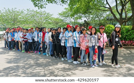 WUXI, CHINA - April 18, 2016: Group of students at Turtle Head Park in Wuxi. Turtle Head Park is the cityâ??s most attractive park and best place to admire the beauty of this lake. - stock photo