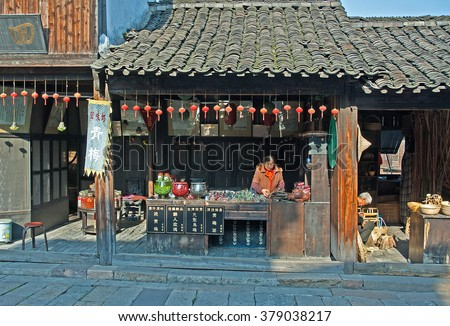 WUZHEN, SHANGHAI-DECEMBER 2, 2008: lady running an old snack shop. Wuzhen water village is Shanghai tourist attraction with more than 100000 visitors per year. - stock photo