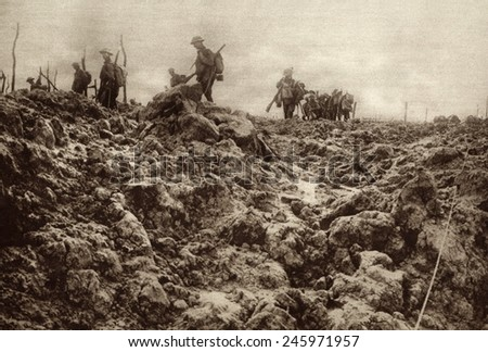 WWI. Western front battleground has been churned up by shell explosions so that it bears no resemblance to its peacetime appearance. Allied soldiers are in the background. Ca. 1915-18. - stock photo