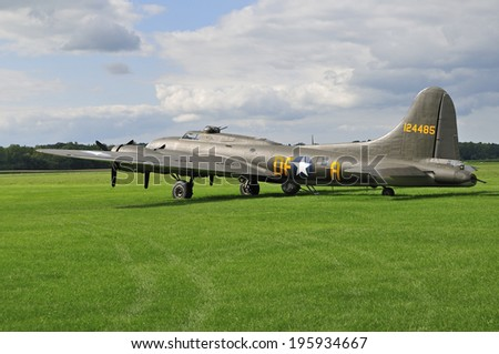 WWII bomber aircraft sitting on a grassy field - stock photo