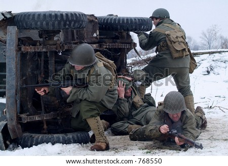 WWII Soldiers in a winter setting. (firing back, from behind a cover of a burning jeep) - stock photo
