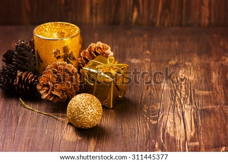 X-mas greeting card: golden candle, pine cones and christmas decorations over old brown wooden background. Selective focus. Vintage style - stock photo