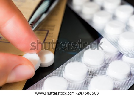 X-ray examination, a prescription, hand takes pills, a pen on the recipe. Focus on the pills - stock photo