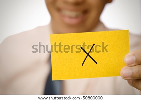 X sign on yellow card holding by businessman. - stock photo