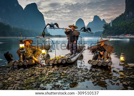 XINGPING, CHINA - OCTOBER 23, 2014: Cormorant fisherman on the ancient bamboo boat with a lighted lamps and cormorants - The Li River, Xingping, China - stock photo