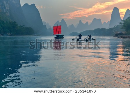 XINGPING, CHINA - OCTOBER 22, 2014: Fisherman stands on traditional bamboo boats at sunrise (boat with a red sail in the background) - The Li River, Xingping, China - stock photo