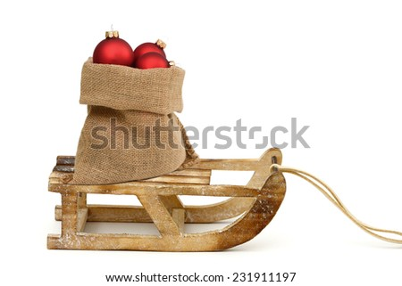 Xmas balls in santa bag on wooden sled - stock photo