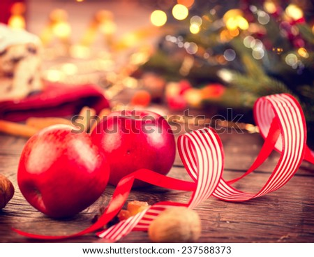 Xmas holiday table setting, decorated with garlands, baubles, wallnuts, hazelnuts, cinnamon sticks. Warm colors toned. Christmas Stollen. Traditional Sweet Fruit Loaf with Icing Sugar  - stock photo