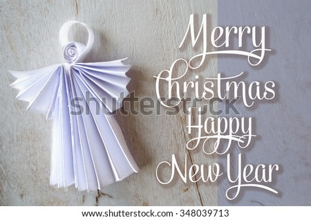 Xmas postcard with hand made paper angel and congratulation. Happy New Year and Merry Christmas greeting card with angel on wooden background. Holidays template. - stock photo
