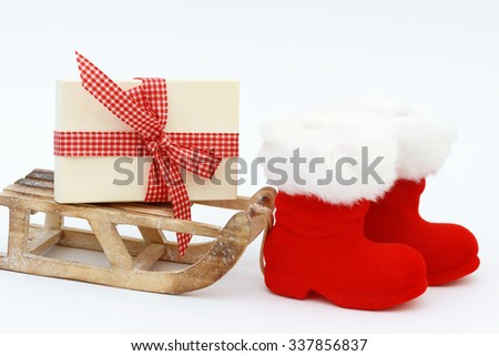 Xmas present and Christmas boots on white - stock photo