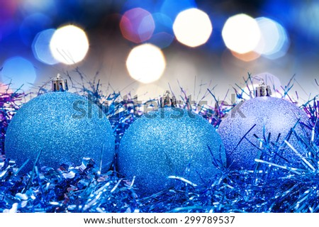 Xmas still life - blue balls, tinsel with blurred blue and violet Christmas lights background - stock photo