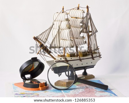 Yacht, a compass and magnifying glass on the wold map - stock photo