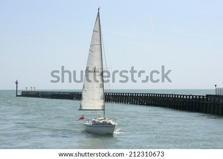 Yacht approaching the harbour at Littlehampton in West Sussex. England. With no visible people. - stock photo