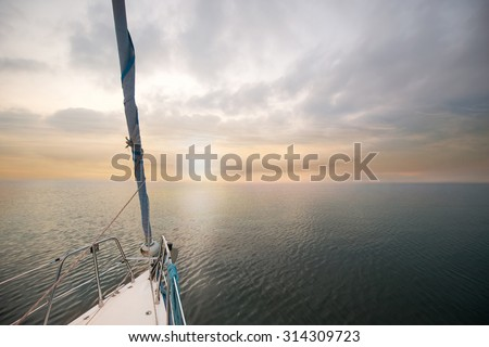 Yacht at sunset. Yacht in the open ocean. Nose of yachts at sunset. Yachting on the sea. - stock photo