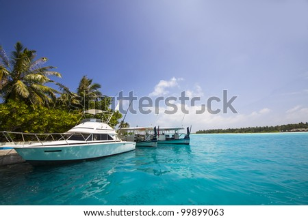 yacht at the jetty in front of a tropical island with palms - stock photo