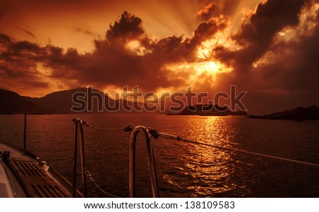 Yacht deck on red dramatic sunset, peaceful seascape, marine adventure, summer holiday, yachting sport, freedom and recreation concept - stock photo