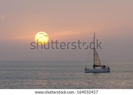 Yacht on the ocean sunset background - stock photo