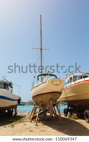 yacht on the shore for storage and repair - stock photo