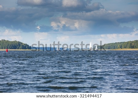 Yacht or boats on beautiful lake in Mazury lake district. Mamry lake in Poland with sailboats photographed i early autumn. - stock photo
