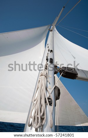 Yacht sail and mast with blue cloudless sky in the background - stock photo