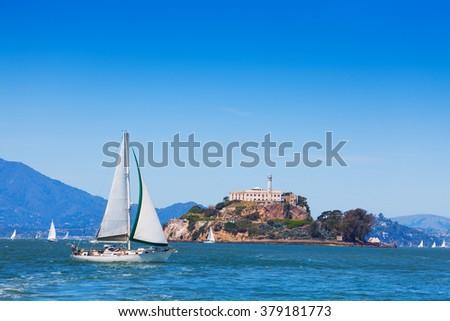 Yacht sail in front of Alcatraz prison island - stock photo