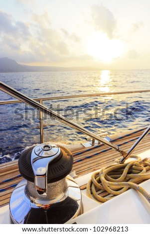 Yacht sailing along the coast at sunset - stock photo