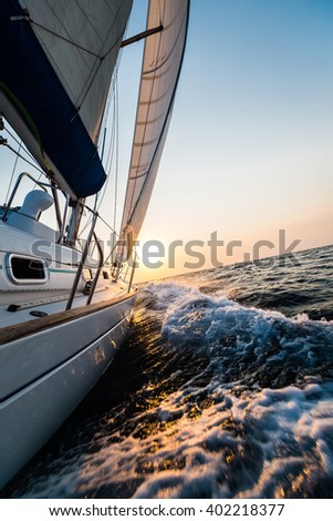 Yacht sailing in open sea at sunset - stock photo