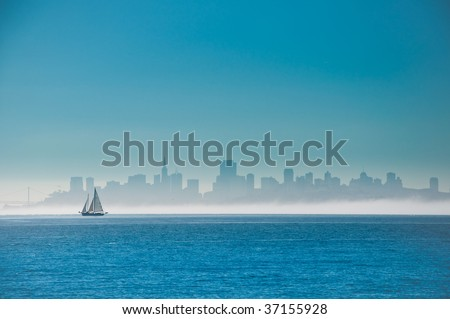 Yacht sailing on San Francisco Bay with the city skyline behind. - stock photo