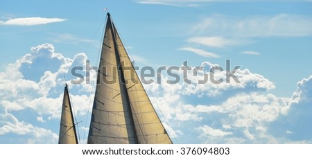 Yacht sails against sky on a sunny day - stock photo