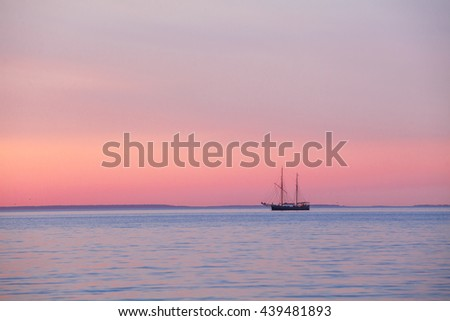 Yacht swimming in Baltic sea at sunset - stock photo