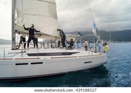 "Yacht team removes the sail. Tivat, Montenegro - 28 April, 2016. Regatta ""Russian stream"" in God-Katorskaya bay of the Adriatic Sea off the coast of Montenegro. - stock photo"